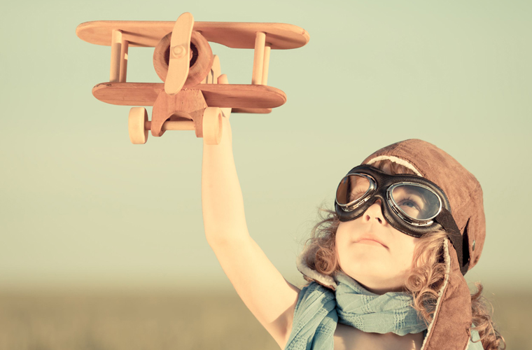 kid with aviator goggles and wooden plane shutterstock_139773448 760x500