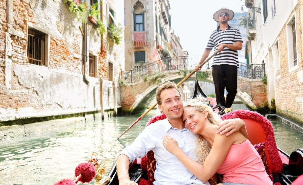 Romantic travel couple in Venice on Gondole ride romance in boat happy together on travel vacation holidays. Romantic young beautiful couple sailing in venetian canal in gondola. Italy, Europe.
