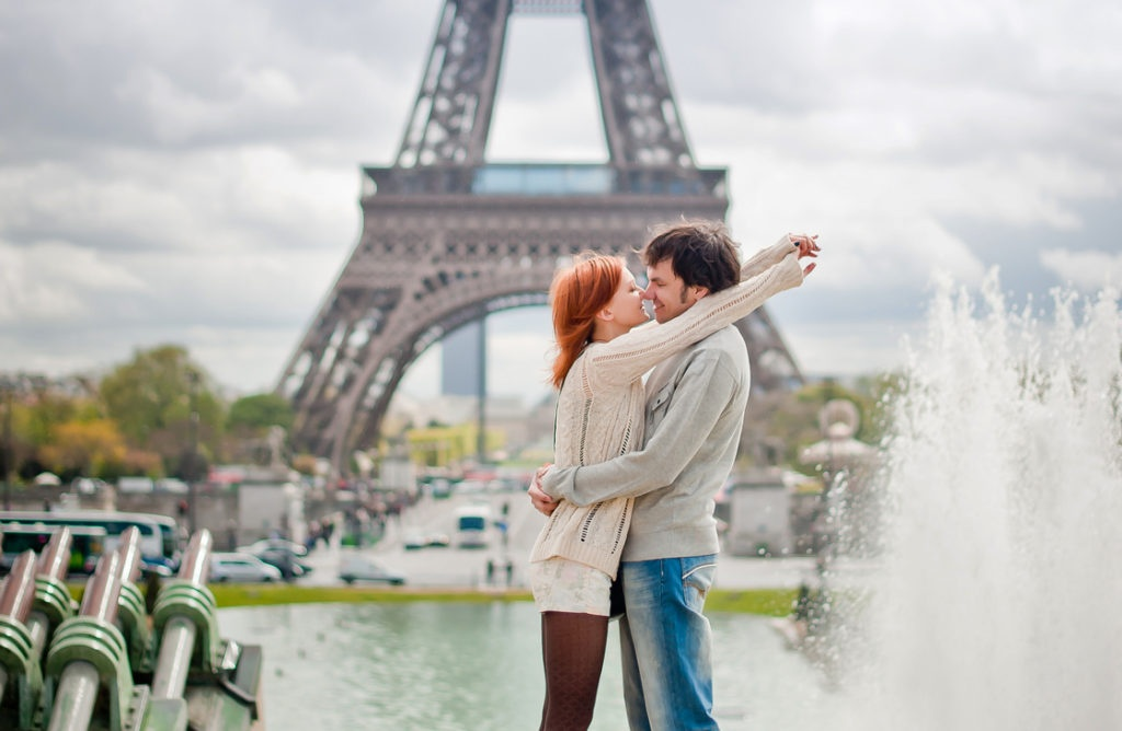 Lovers kissing in Paris with the Eiffel Tower in the Background